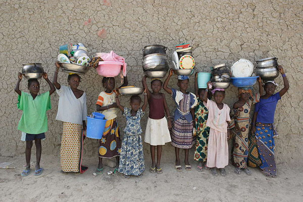Women and girls carrying pots and pans